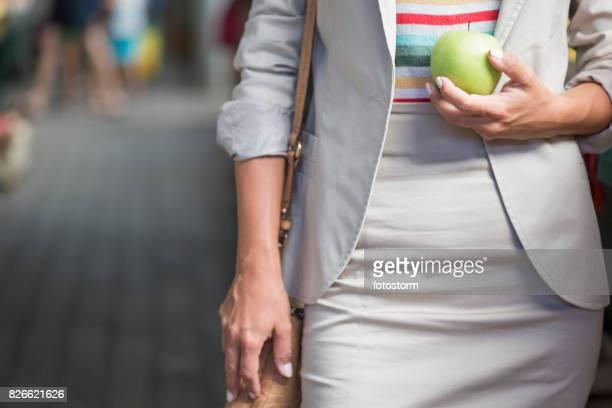 jovem mulher segurando o apple - mid section - fotografias e filmes do acervo
