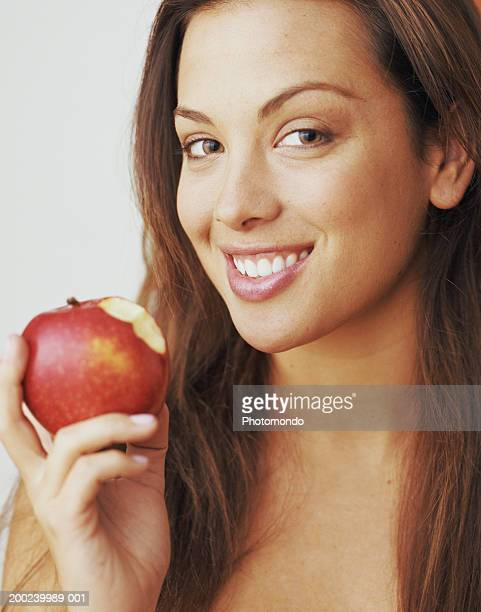 Young woman holding apple, smiling, close-up, portrait