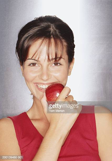 Young woman holding apple to mouth, smiling, portrait