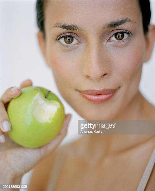 Young woman holding apple with bite taken out, portrait