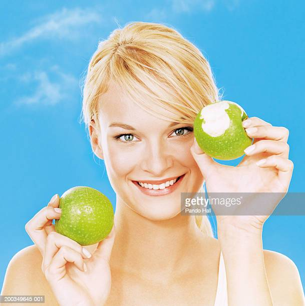 Young woman holding apples, smiling, portrait, close-up