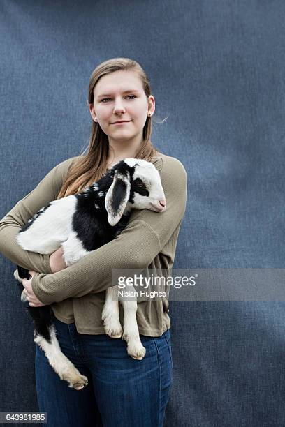 young woman holding baby goat