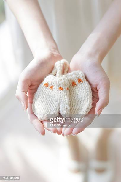 Young woman holding baby mittens