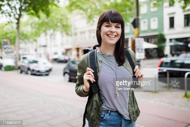young woman holding back back on her way to the shops - une seule femme d'âge moyen photos et images de collection