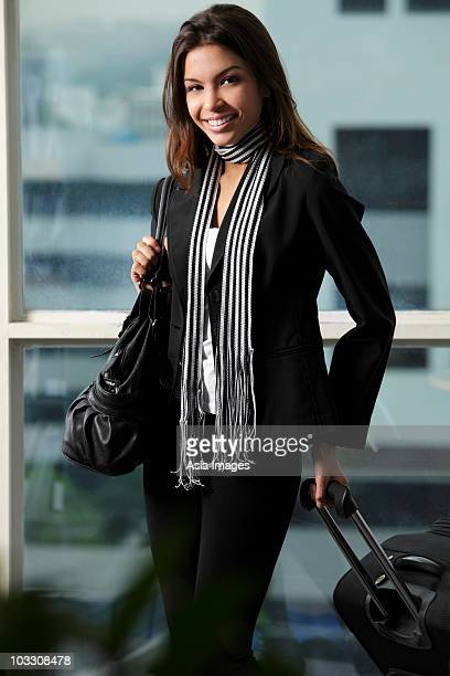 young woman holding bag and pulling suitcase