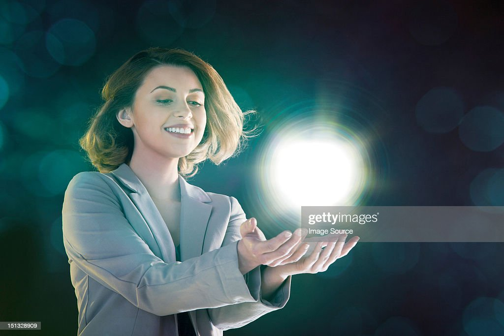 Young woman holding ball of light : Stock Photo