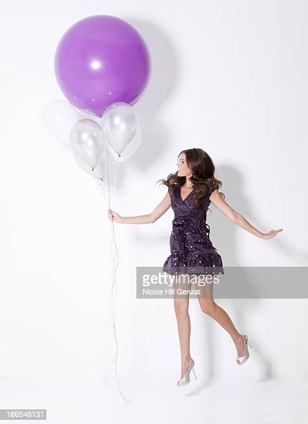 young woman holding balloons, floating at party - una sola mujer joven fotografías e imágenes de stock
