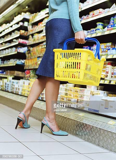 young woman holding basket in supermarket aisle, low section - parte inferior imagens e fotografias de stock