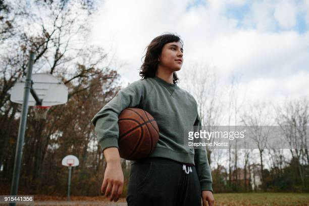 Young woman holding basketball in outdoor court