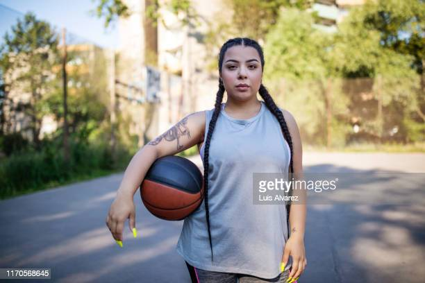 young woman holding basketball on court - basketball sport stock pictures, royalty-free photos & images