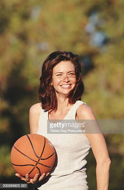 Young woman holding basketball outdoors, smiling