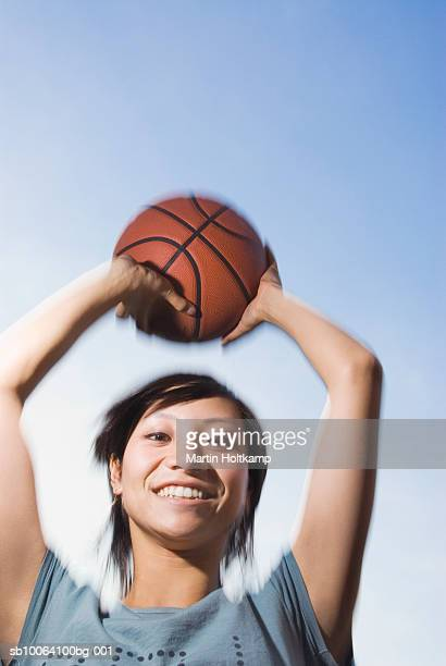 Young woman holding basketball up in air, portrait, low angle view