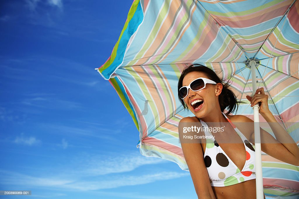 Young woman holding beach umbrella, smiling, close-up : Stock-Foto