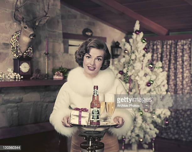 Young woman holding beer and gift in tray, smiling, portrait