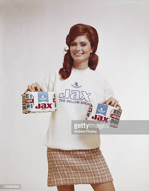 Young woman holding beer boxes, smiling, portrait