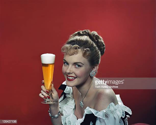 Young woman holding beer glass, smiling, portrait