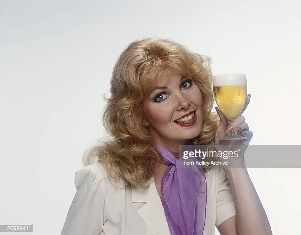 Jeune femme tenant le verre de bière, souriant, portrait