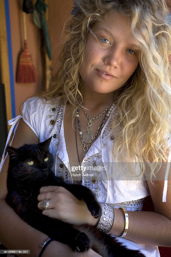 Young woman holding black cat, close-up, portrait : Stockfoto