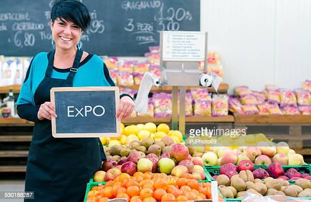jovem mulher segurando a placa de quadro-negro com expo - mercado espaço de venda no varejo - fotografias e filmes do acervo