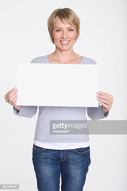 Young woman holding blank white board, portrait