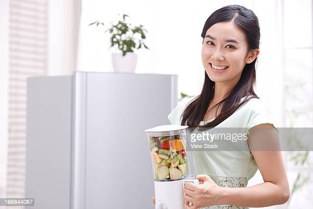Young woman holding blender in kitchen
