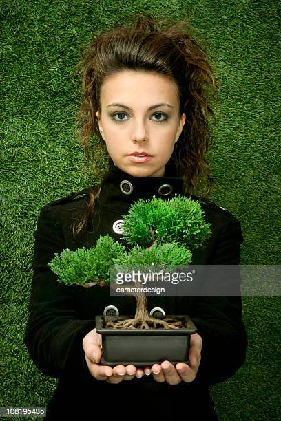 young woman holding bonsai tree against grass background - ecologist stock pictures, royalty-free photos & images