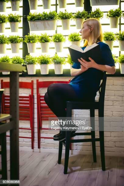 Young Woman Holding Book Against Potted Plants At Greenhouse