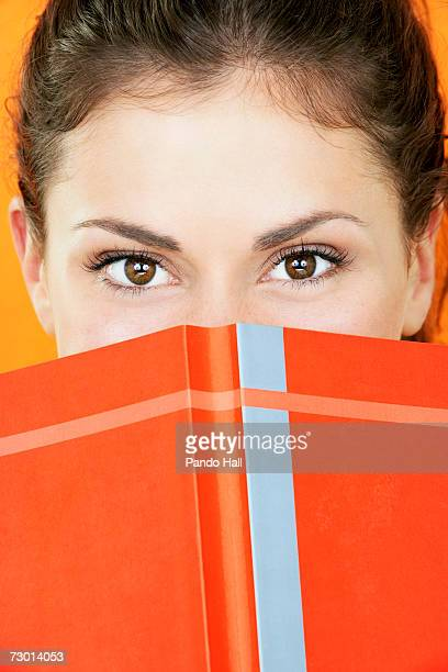 Young woman holding book in front of face, close-up, portrait