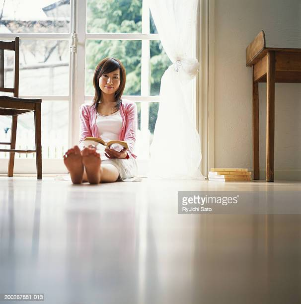 young woman holding book, smiling, ground view - japanese women feet stock photos and pictures