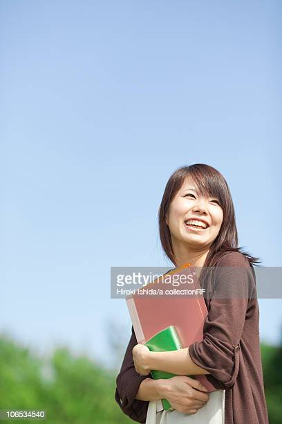 young woman holding books, japan - 女子大生 ストックフォトと画像