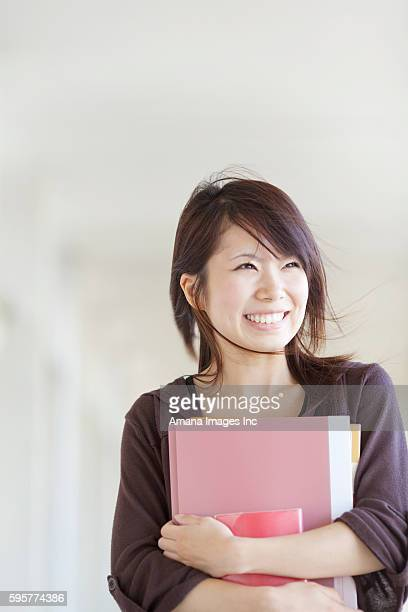 Young woman holding books, Japan