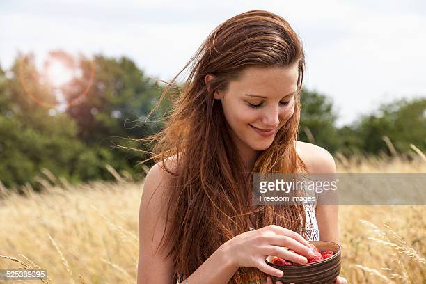 Young woman holding bowl of fresh fruit in field