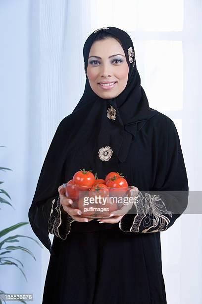 Young woman holding bowl tomatoes in bowl,portrait