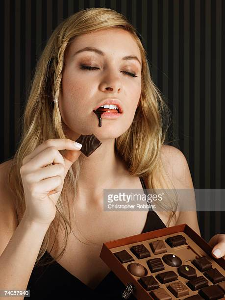 Young woman holding box of chocolates, chocolate dripping down chin