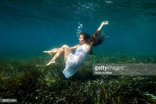 Young woman holding breath in water