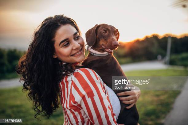 young woman holding brown dachshund - off leash dog park stock pictures, royalty-free photos & images
