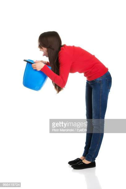 young woman holding bucket while standing against white background - vomit stock pictures, royalty-free photos & images