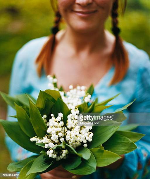 Young woman holding bunch of Lilies of the Valley