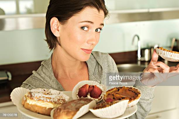 young woman holding cakes - bulimia stock photos and pictures
