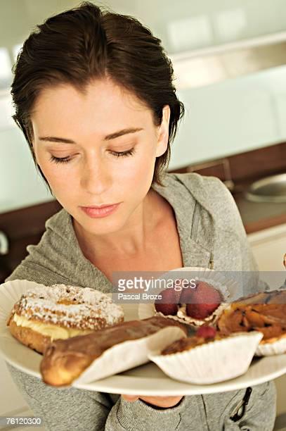 young woman holding cakes - bulimia fotografías e imágenes de stock