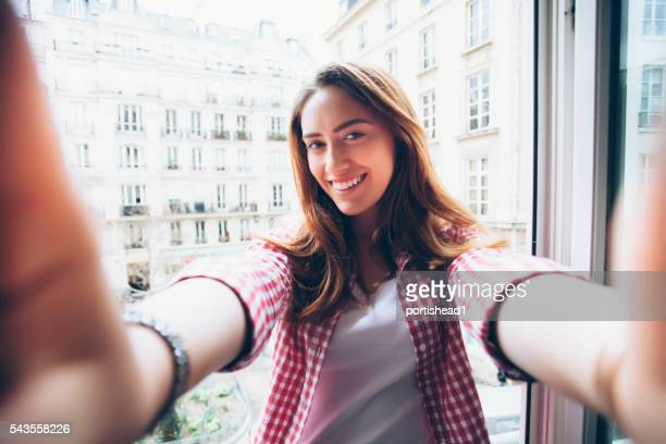 Young woman holding camera and making selfie