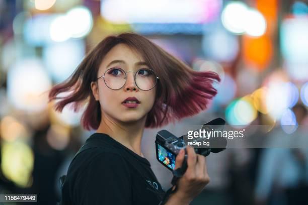 夜にカメラを持つ若い女性 - 背景に人 ストックフォトと画像