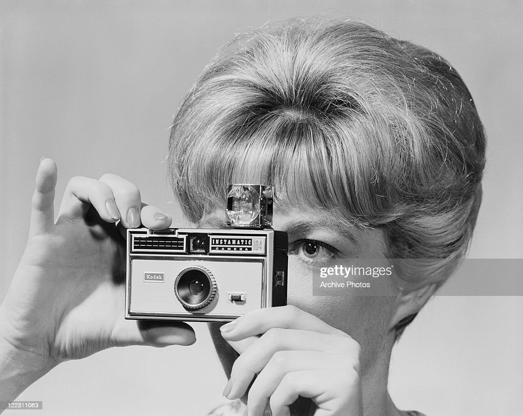 Young woman holding camera, close-up : Stock Photo