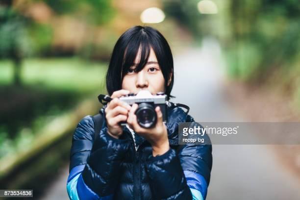 自然でカメラを保持している若い女性