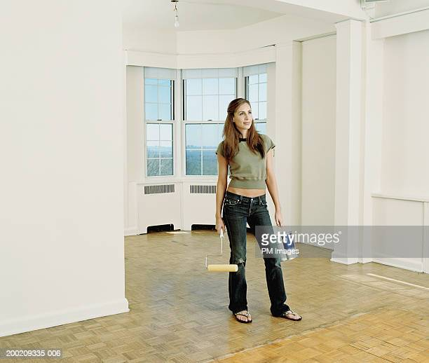 Young woman holding can of paint and roller in empty room