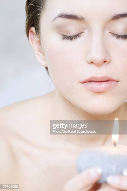 Young woman holding candle, eyes closed, cropped view