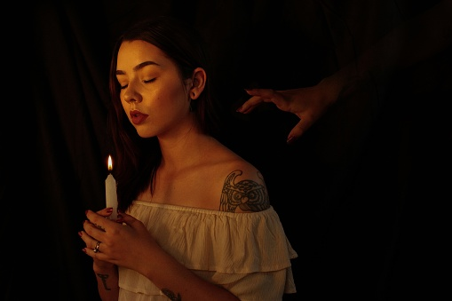 Young Woman Holding Candle While Standing In Darkroom - gettyimageskorea