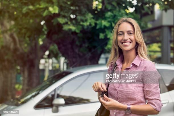 young woman holding car keys, smiling cheerfully - bovenlichaam stockfoto's en -beelden