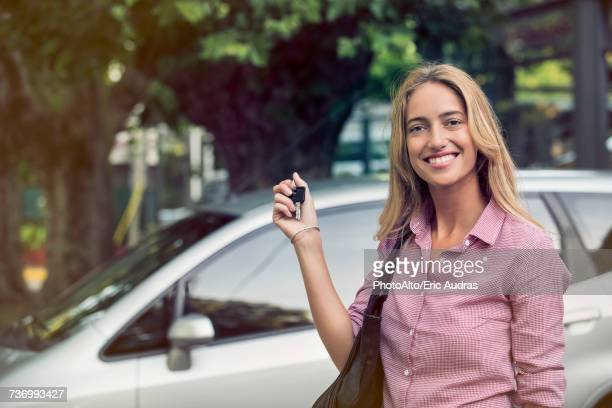 Young woman holding car keys, smiling cheerfully, portrait