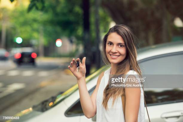Young woman holding car keys, smiling, portrait